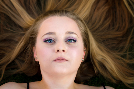 spread around: A beautiful teenage girl lays on the ground with her long, blond hair spread out around her.  She looks blankly up at the camera with just a hint of a smile in her eyes. Stock Photo