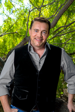 collared shirt: A man in a collared shirt and suede vest leans against a tree for a portrait.  He has bright, blue eyes and a nice smile.