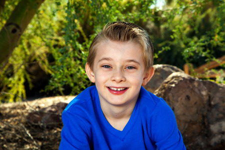 approachable: Outdoor portrait of a young boy in blue.  He is smiling and looks approachable.