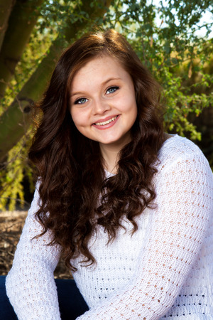 dimples: A beautiful teenage girl with big, blue eyes, dimples, and brown hair poses for a portrait.