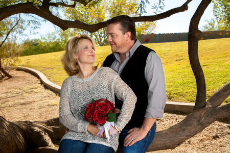 gaze: A couple celebrates their anniversary.  The wife holds a rose bouquet to symbolize her wedding flowers.  They gaze into each others eyes and she tries not to laugh. Stock Photo