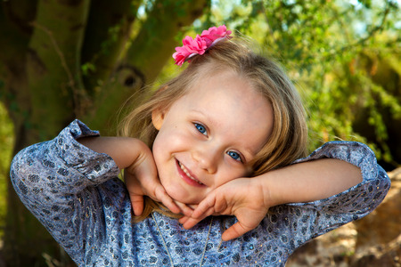 tilted: A sweet little girl with blond hair and blue eys poses with her hands under her chin.  Her head is tilted to the side and she has a sideways grin.