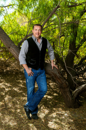 open collar: A trendy man leans on a tree in a suede vest while posing for his portrait.