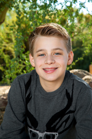good looking boy: Portrait of a blond, tween boy smiling at the camera outdoors.