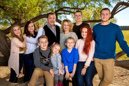 Portret van een groot gezin in het park, onder een boom. Ouders met hun acht kinderen. Drie broers en zussen fours zorgt voor veel broers en zussen.