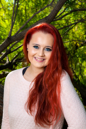 teenaged girl: A beautiful, teenaged girl with dyed red hair poses for a portrait in front of trees.  She has a tilted head, lovely smile, and bright, blue eyes.