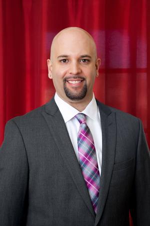 pierced ears: Portrait of a groom in a grey suit and pink and grey tie.  He has a chin beard.