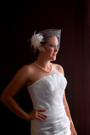 Stunning bride in a birdcage veil standing in window light with her hand on her hip.