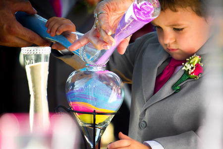 mixed marriage: A ring bearer, who is the son of the bride, pours colored sand in the unity ceremony during a wedding.