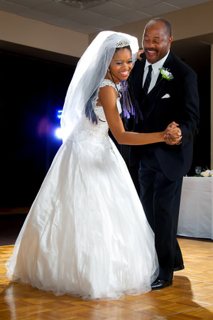 An African American bride dances with her dad during the father daughter dance at her wedding reception. 版權商用圖片
