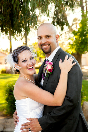 A bride and groom hold each other and laugh while looking at the camera.  They are happy and posed but unposed at the same time.