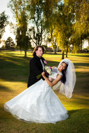 a newly married couple: A newly married couple has a little fun, dancing around after their wedding.  The groom is dipping his bride and they smile at the camera.  Beautiful, afternoon light on a golf course.