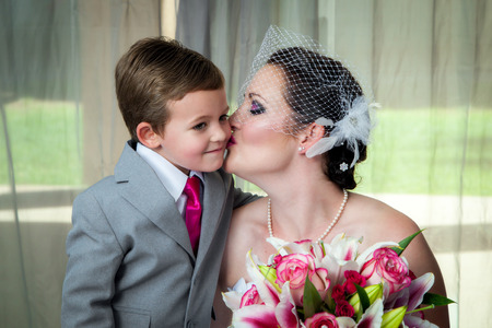 prewedding: A young bride kisses her son on her wedding day in her pre-wedding portrait.  She holds her bouquet and he leans in for a kiss. Stock Photo