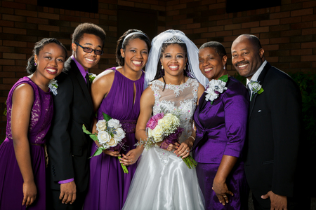 american: A beautiful African American bride poses for a picture with her family before her wedding. Stock Photo