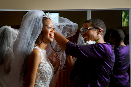 Mother of the bride adjusts her daughterâ??s veil on her wedding day.  Beautiful, African American women, smiling while getting the daughter ready for her wedding. Banco de Imagens