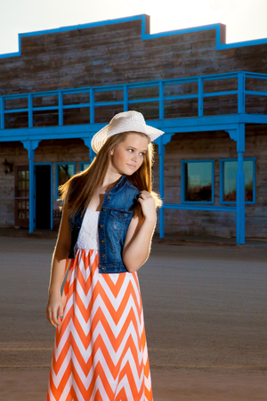 denim skirt: A teenage cowgirl wearing a long, chevron pattern skirt and denim jacket with a western hat plays with her long, back lit hair as she glances over her shoulder.