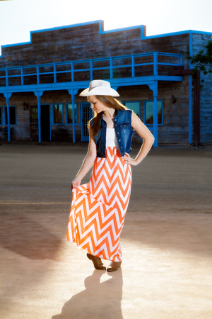 curtsy: A teenage cowgirl looks down as she gives a little curtsy.  She is wearing a western hat, boots, and a long, modern skirt. Stock Photo