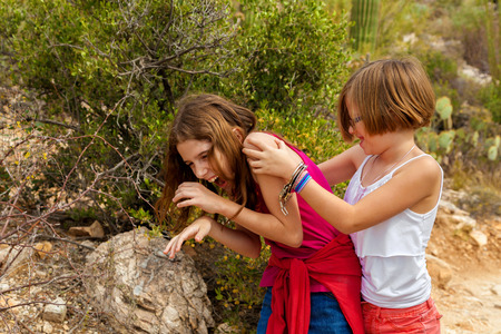 silliness: Typical sisters play fighting while laughing.  One is wearing a set of play handcuffs as a bracelet.  They are in the Arizona desert.