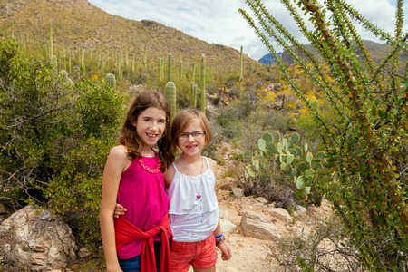 Two young girls posing for a picture in the Arizona desert.  One blond and one brunette.