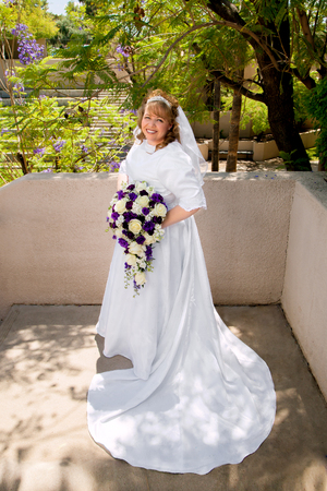 curvy: A beautiful, curvy bride, poses with white and purple roses.