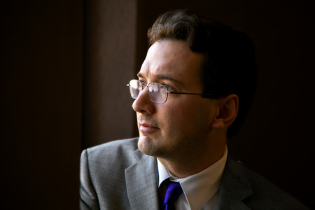 room accent: A pensive groom with glasses sits, looking out a window, on his wedding day. Stock Photo