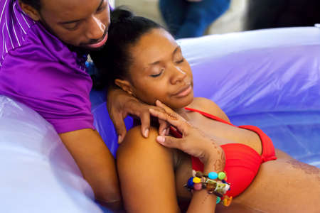 birthing: A beautiful African American woman labors peacefully in a birthing tub as her husband comforts her by holding her hand and rubbing her back.