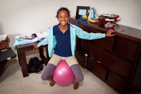 home birth: A young African American girl balances on her mothers birthing ball during a home birth as she anticipates the arrival of her baby sister.