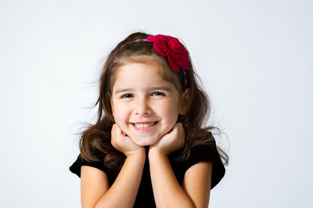 chin on hands: A cute, young girl grins with her chin in her hands.
