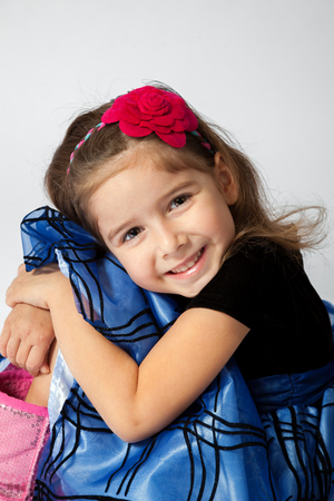 A sweet little girl hugs her knees while posing for a portrait. Banco de Imagens