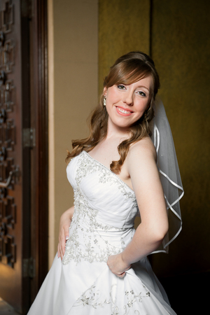 A three quarter pose of a beautiful bride.  She is slightly turned ot the side, holding her dress in one hand with her hip pushed out.