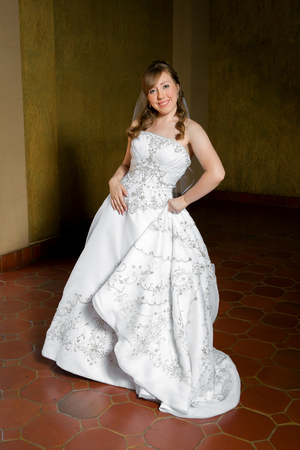 sassy: A bride poses with a pleasing curved spine.  One hand holds her dress and the other rests gently on her hip.  She looks sweet and sassy.
