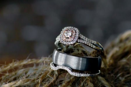 tied down: A bride�??s wedding and engagement band sandwich the groom�??s ring.  All three are tied together with twine ready to go down the aisle to symbolize a beautiful union. Stock Photo