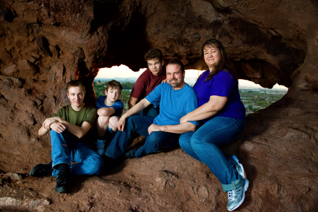 good looking teenage guy: A family of five with three teen boys poses for a portrait in a natural rock window in Arizona. Stock Photo