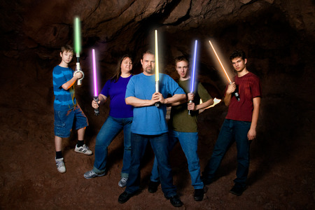 fanatics: A science fiction loving family poses for a family portrait with pretend light swords in this composite image.