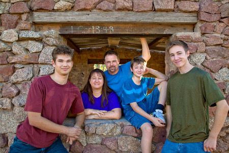 good looking teenage guy: A family of five, with three boys, poses for a portrait in front of a rock structure.