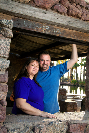 cor: A loving couple poses under a I Cor 13:4-8 sign at a park ramada.