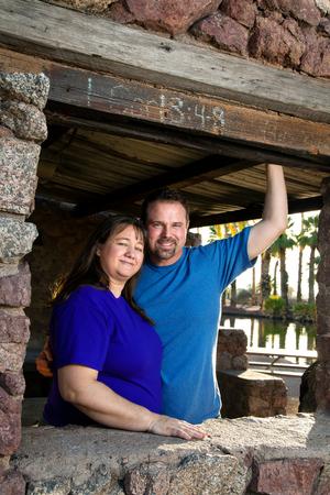 cor: A loving couple poses under a I Cor 13:4-8 sign at a park ramada.