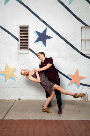 kick around: A young couple in love plays around on an urban street, dancing and dipping.  He looks at her and she smiles for the camera. Stock Photo