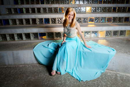 A beautiful, blond, teen girl sits in front of glass block admiring her prom dress which is spread out around her.  She looks like a princess.
