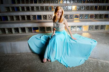 Een mooi, blond, tienermeisje zit voor glasblok bewonderend haar promkleding die rond haar wordt uitgespreid. Ze ziet eruit als een prinses.