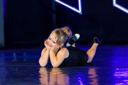 An adorable little tap dancing girl lays on the stage with her chin in her hands and her head tilted to the side, kicking her feet.  The stage lights give the image a blue tint.