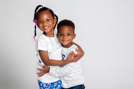 A young African American girl in braids hugs her little brother.  Both are smiling for their portrait against a white backdrop. Stock Photo