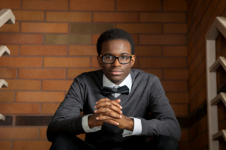 A confident african american teenager wearing a bowtie sits in front of a brick wall and leans forward, resting on his knees. Stok Fotoğraf