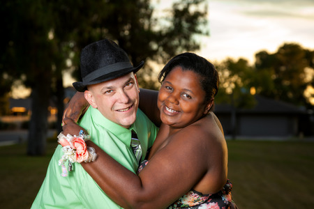 A happy interracial couple poses for a portrait before an adult prom.  She is wearing a corsage. Stock Photo
