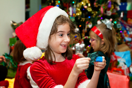 A little girl has an excited expression as she holds up a piece of wrapped chocolate on Christmas morning.  She is wearing a Santa hat and dress.