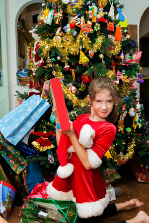 A young girl holds up her Christmas present with a smirky, proud look on her face.  She is kneeling in front of the decorated Christmas tree, wearing a santa dress.