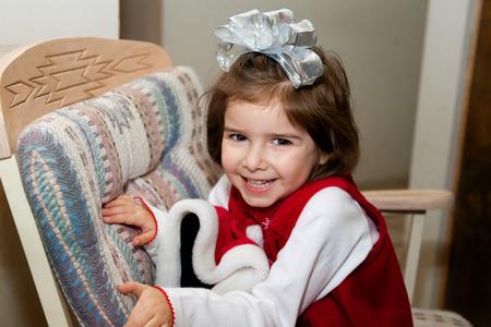 非常に興奮している若い女の子は、クリスマスの朝に椅子の後方に座っています。 彼女は熱心で朝食を取得し、贈り物を開きます。 彼女の頭の上に 写真素材