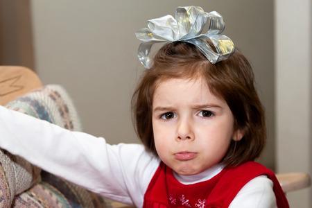 不機嫌そうな、ぽってりした顔をした少女がクリスマスの朝。 彼女は、彼女の頭の大きな、銀の弓としわを寄せた彼女の eybrows と彼女の下唇を突き 写真素材