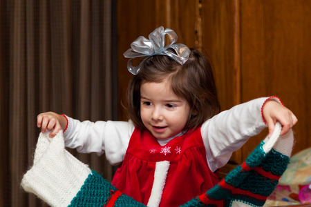 A little girl hold her giant, empty stocking on Christmas morning after she has emptied it.  She is happy. Stock Photo