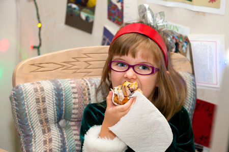 A young girl wearing a green, winter dress and red headband with a silver bow and pink glasses eats a huge cinnamon bun for breakfast on Christmas morning. Stock Photo